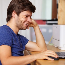 Young handsome guy with laptop next to table in room, background