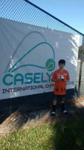 Rafael veste a camisa do SUPERA comemorando troféu do torneio Casely International