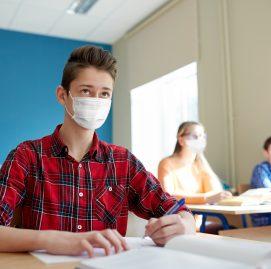Menino sentado na sala de aula usa máscara e assiste aula