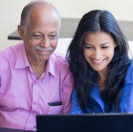 Homem idoso ao lado de mulher aprendendo no computador