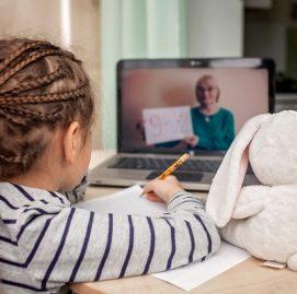 Menina com tranças no cabelo assiste aulas no computador com coelho de pelúcia ao lado