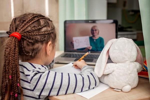 Menina com tranças no cabelo assiste aula pelo computador com seu coelho de pelúcia ao lado