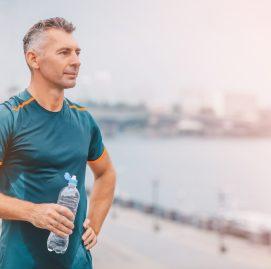 Homem suado segura garrafa de agua e olha para o horizonte