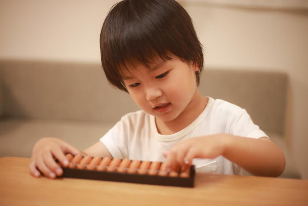 Criança manuseando o ábaco japonês.