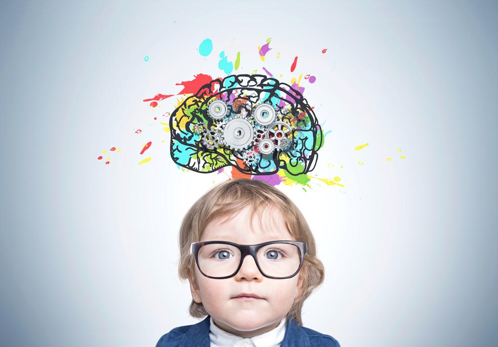 Uma criança usando óculos abaixo de uma ilustração colorida de um cérebro para ilustrar a importância da estimulação cognitiva.